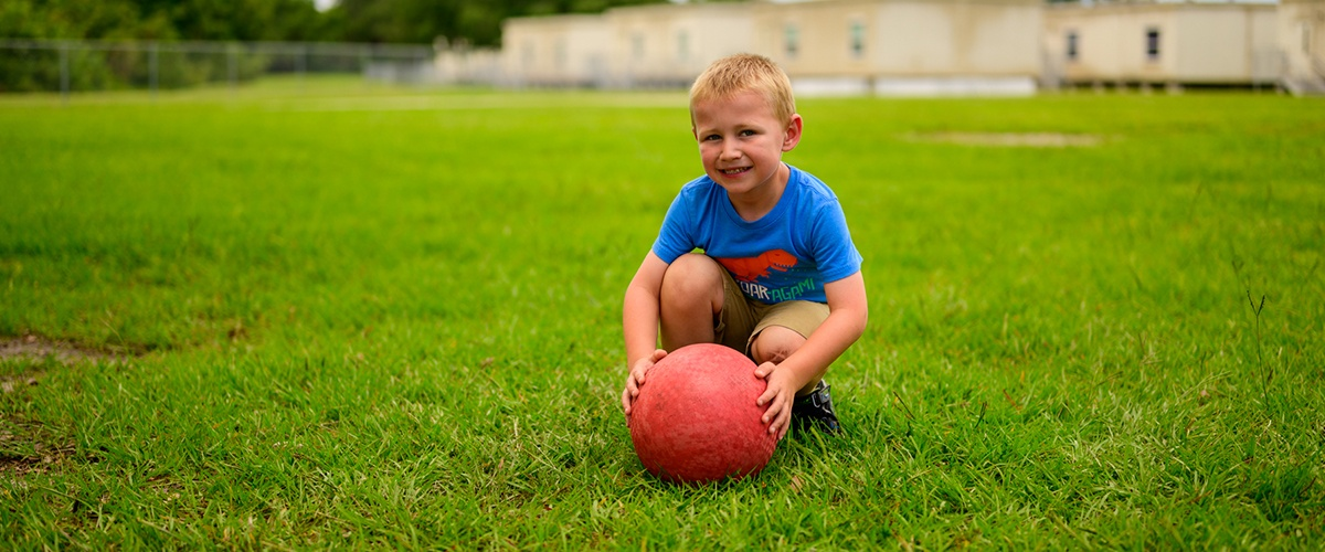 Kid playing outside with a ball